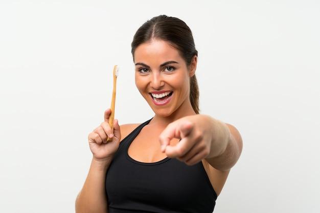 Jonge vrouw over geïsoleerde witte muur die haar tanden borstelt