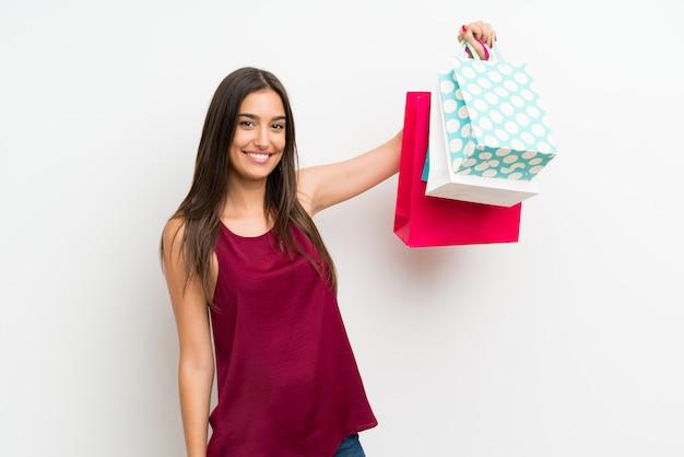 Jonge vrouw over geïsoleerde witte muur die heel wat het winkelen zakken houdt