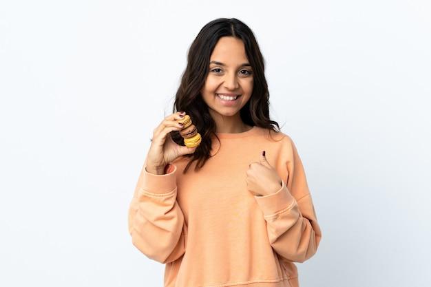 Jonge vrouw over geïsoleerde witte muur die kleurrijke franse macarons houdt en met verrassingsuitdrukking