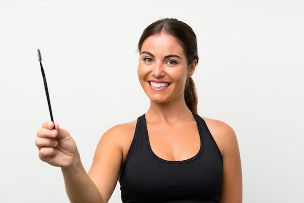 Jonge vrouw over geïsoleerde witte muur die mascara met kosmetische stormloop toepast