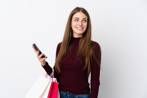 Jonge vrouw over geïsoleerde witte muurholding het winkelen zakken en een mobiele telefoon