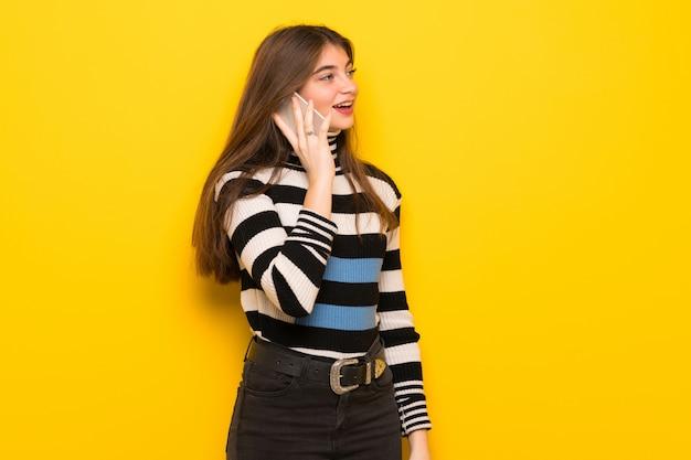 Jonge vrouw over gele muur die een gesprek met de mobiele telefoon houdt