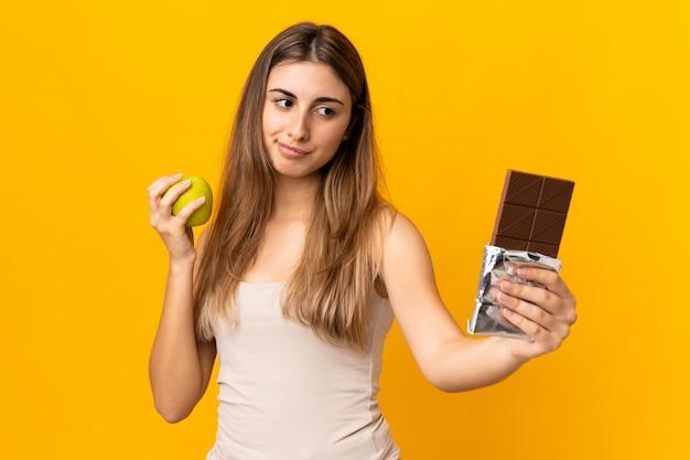 Jonge vrouw over gele muur die twijfels heeft terwijl het nemen van een chocoladetablet in de ene hand en een appel in de andere