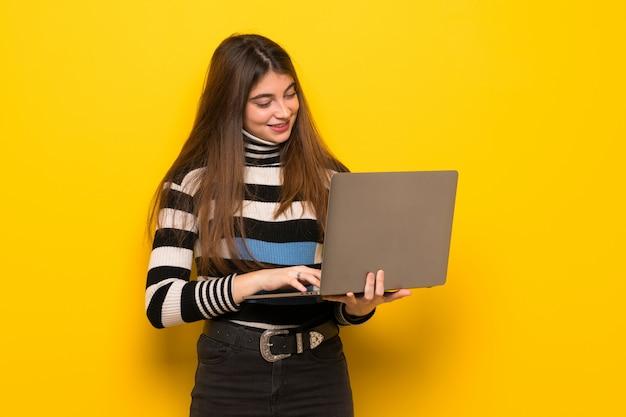 Jonge vrouw over gele muur met laptop