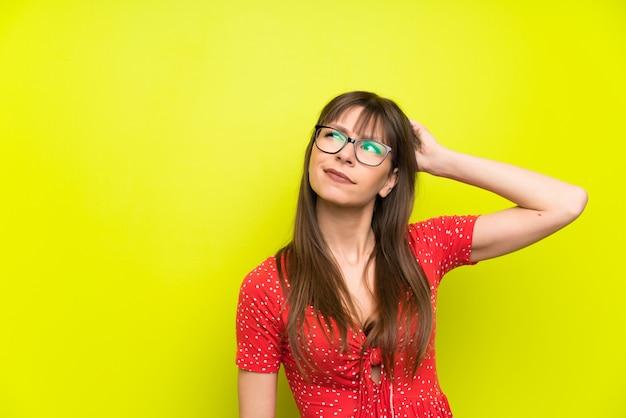 Jonge vrouw over groene muur die twijfels heeft en met verwarde gezichtsuitdrukking
