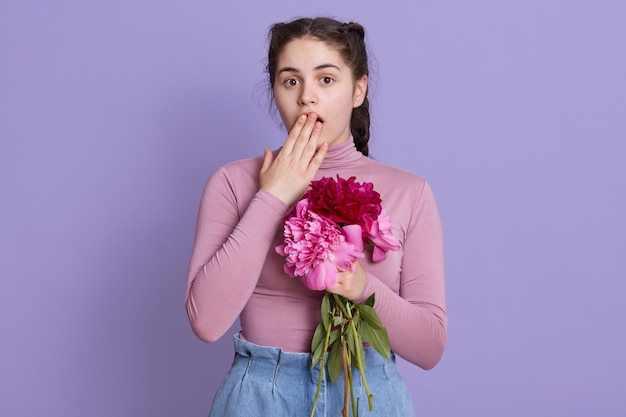 Jonge vrouw over lila muur die casual kleding draagt die bloemen in handen vouwt, geschokt is, mond bedekt met hand voor fout, poseren tegen lila muur.