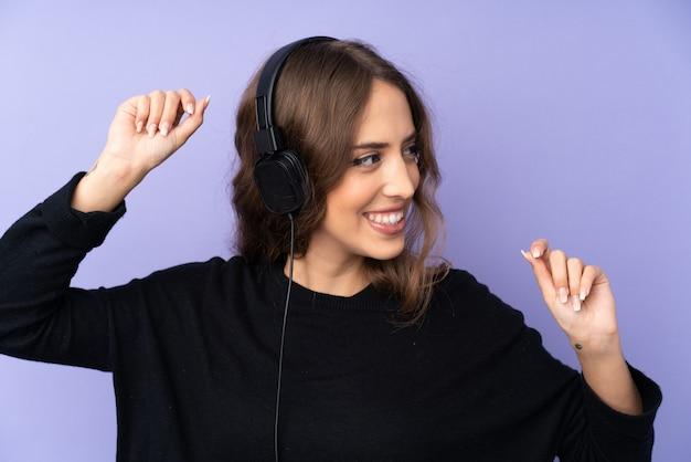 Jonge vrouw over paarse muur luisteren muziek en dansen