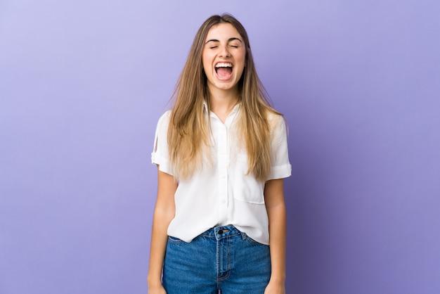 Jonge vrouw over paarse muur schreeuwen naar voren met wijd open mond