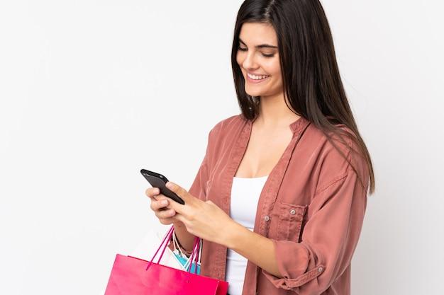 Jonge vrouw over witte muur boodschappentassen houden en het schrijven van een bericht met haar mobiele telefoon naar een vriend
