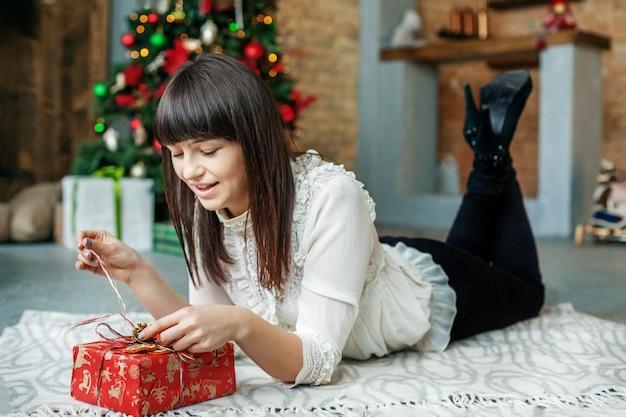 Jonge vrouw pakt geschenkdoos uit. concept nieuwjaar, vrolijk kerstfeest