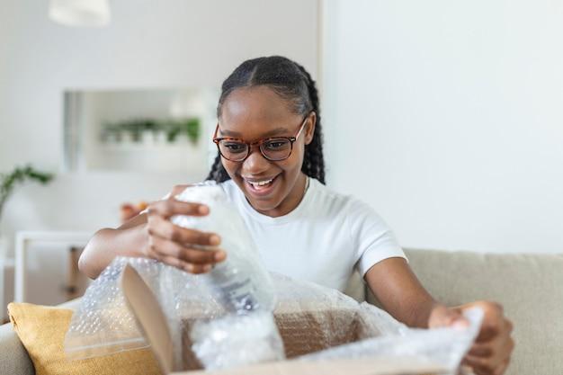 Jonge vrouw pakt het pakket uit dat ze online heeft besteld, afro-amerikaanse vrouw is thuis, ze pakt het afgeleverde pakket uit