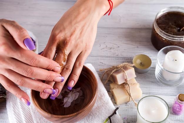 Jonge vrouw past een koffie scrub op handen