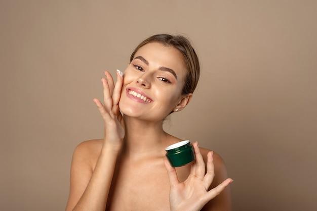 Jonge vrouw past vochtinbrengende crème toe op haar gezicht en glimlacht. huid zorg concept.