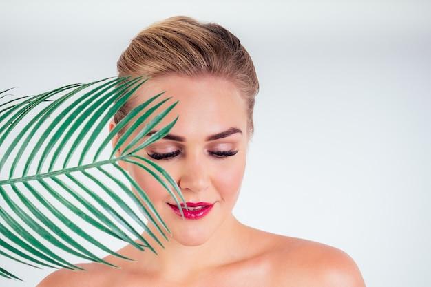 Jonge vrouw perfecte huid make-up met lange wimpers en rode lippenstift met een tropische palm blad close-up schouders naakte kale witte achtergrond in een studio.