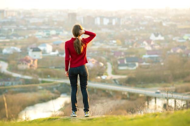 Jonge vrouw permanent buiten genieten van uitzicht op de stad. ontspanning, vrijheid en wellnessconcept.