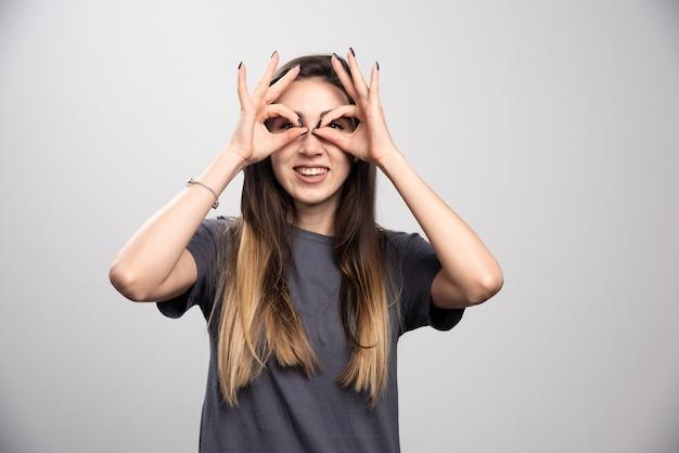 Jonge vrouw permanent en poseren op een grijze achtergrond. hoge kwaliteit foto