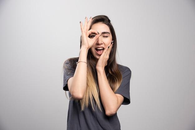 Jonge vrouw permanent en poseren op een grijze achtergrond