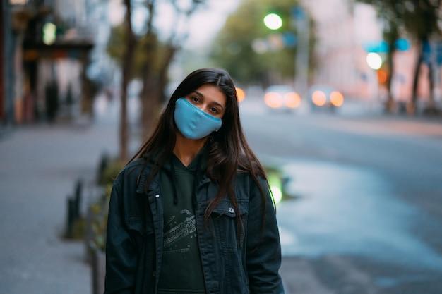 Jonge vrouw, persoon in beschermend medisch steriel masker dat zich bij lege straat bevindt, die camera bekijkt.