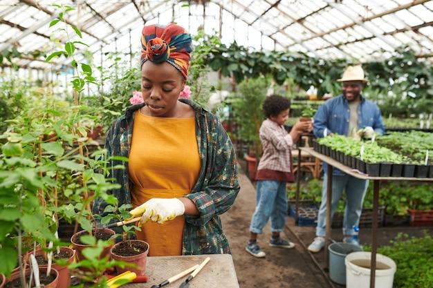 Jonge vrouw plant de zaailingen samen met haar familie op de achtergrond werken ze in de tuin