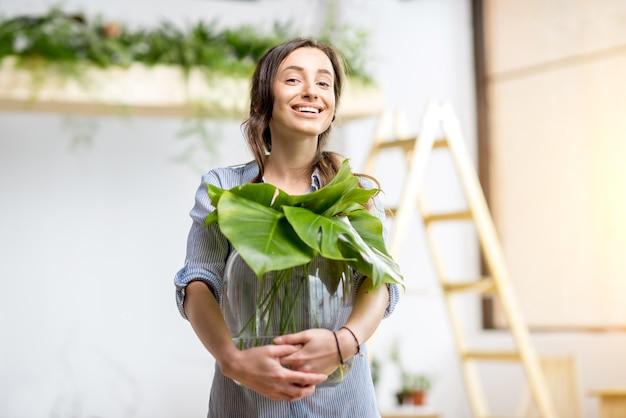 Jonge vrouw plant huis met groen met grote plant in de kamer
