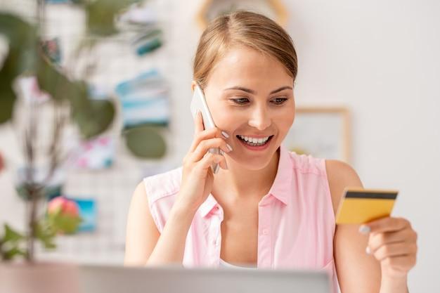 Jonge vrouw plastic kaart kijken tijdens het maken van bestelling in de online winkel en in gesprek met manager door smartphone