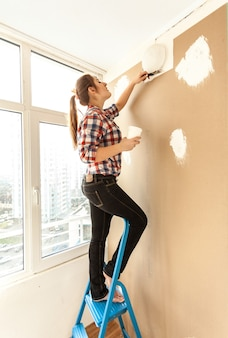 Jonge vrouw pleistermuur op hoge ladder