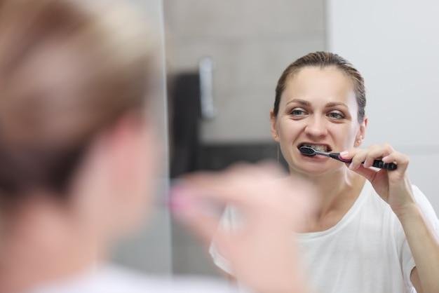 Jonge vrouw poetst haar tanden in de badkamer voor spiegel