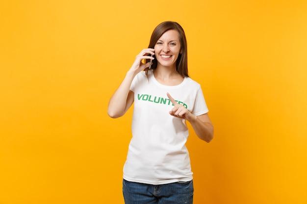 Jonge vrouw portret in wit t-shirt met schriftelijke inscriptie groene titel vrijwilliger praten op mobiele telefoon geïsoleerd op gele achtergrond. vrijwillige gratis hulp, liefdadigheidswerkconcept.
