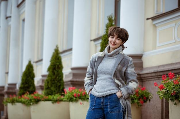 Jonge vrouw poseren buiten in een grijze jas in het voorjaar