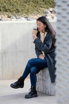 Jonge vrouw poseren buiten terwijl het drinken van koffie