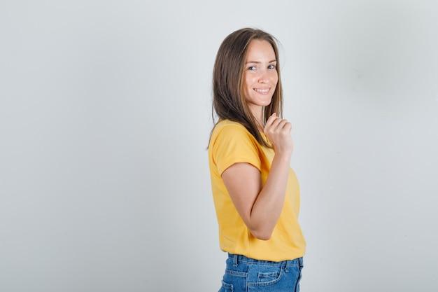 Jonge vrouw poseren en glimlachen in t-shirt, korte broek en op zoek verleidelijk.
