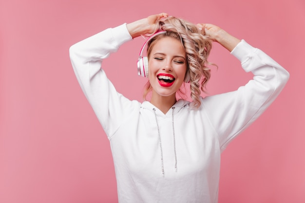 Jonge vrouw poseren en luisteren naar muziek via haar roze koptelefoon