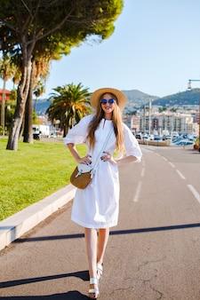 Jonge vrouw poseren en trendy elegante vrouwelijke jurk en stro accessoires dragen