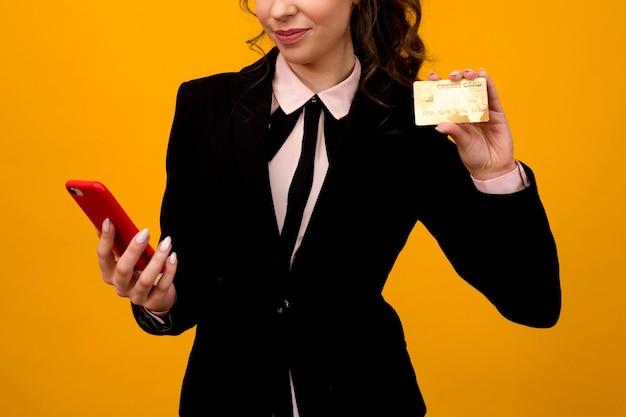 Jonge vrouw poseren geïsoleerd op gele muur achtergrond met behulp van mobiele telefoon met debetkaart