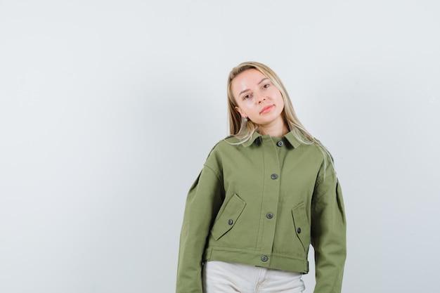 Jonge vrouw poseren in groene jas en schattig op zoek. vooraanzicht.