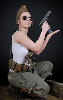Jonge vrouw poseren in militair uniform en een wapen