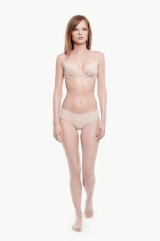 Jonge vrouw poseren in ondergoed, beige beha en slipje, perfecte huid