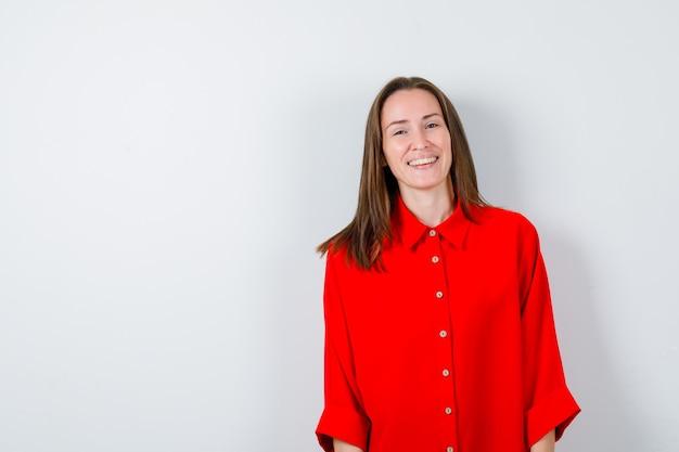 Jonge vrouw poseren in rode blouse en op zoek gelukkig. vooraanzicht.