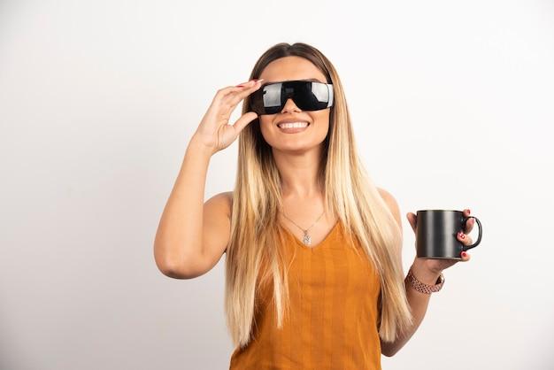 Jonge vrouw poseren met bril en zwarte kop.