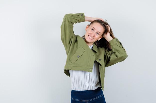 Jonge vrouw poseren met de handen op het hoofd in shirt en er vrolijk uitzien. vooraanzicht.