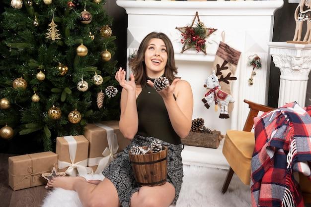 Jonge vrouw poseren met dennenappels in de buurt van de kerstboom