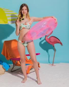 Jonge vrouw poseren met drijvende ring op strand