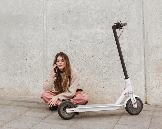 Jonge vrouw poseren met een elektrische scooter