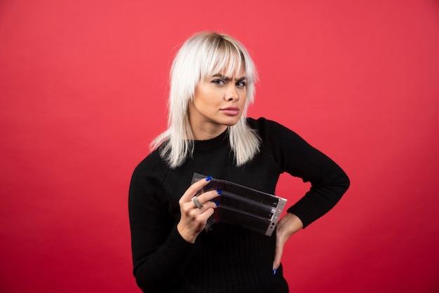 Jonge vrouw poseren met een fotoband op een rode achtergrond