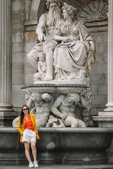 Jonge vrouw poseren met een standbeeld