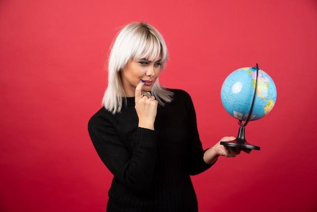 Jonge vrouw poseren met een wereldbol op een rode achtergrond. hoge kwaliteit foto Gratis Foto