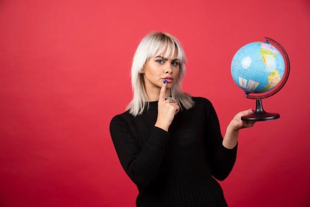 Jonge vrouw poseren met een wereldbol op een rode achtergrond. hoge kwaliteit foto