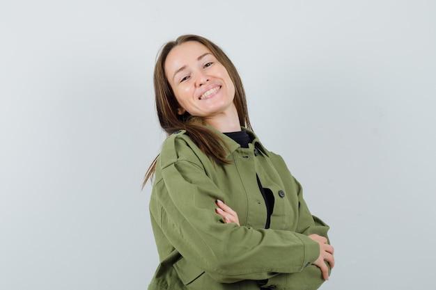 Jonge vrouw poseren met gekruiste armen in groene jas en op zoek vrolijk, vooraanzicht.
