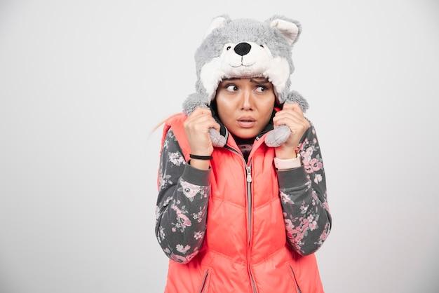 Jonge vrouw poseren met grappige hoed op een witte muur