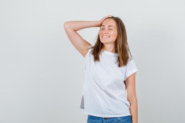 Jonge vrouw poseren met hand op hoofd in wit t-shirt, korte broek en op zoek vrolijk. vooraanzicht.